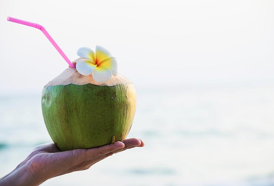 image d'une personne tenant un cocktail sur la plage
